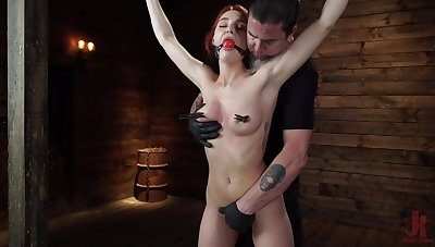 Smiling redhead model Lacey Lennon gets turned on encircling bondage